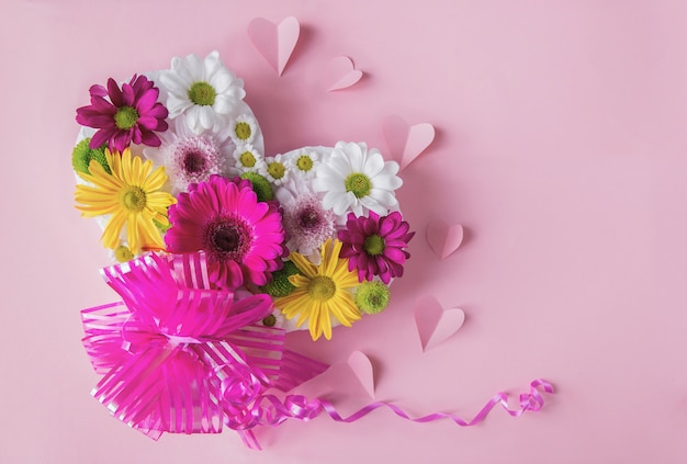 Pink floral background with colorful fresh heart shaped daisies and gift bow and paper hearts