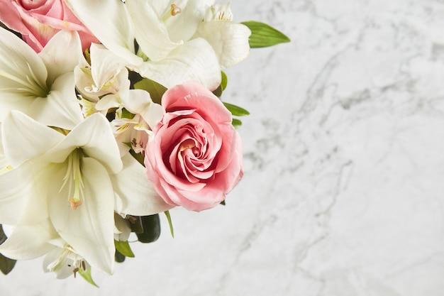 大理石の背景にピンクの花のアレンジメント。