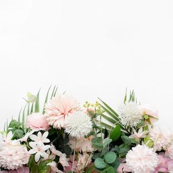 白い背景の上のヤシの葉とピンクの花の境界線