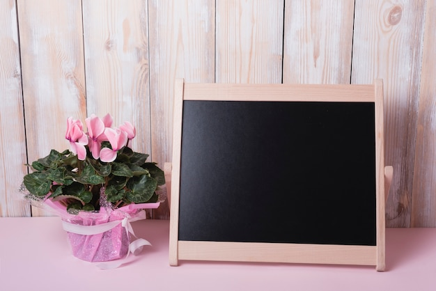 Pink flower bouquet with small blank chalkboard on desk against wooden wall