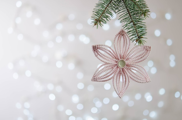 Pink flower hangs on a christmas tree branch. bokeh. christmas decoration