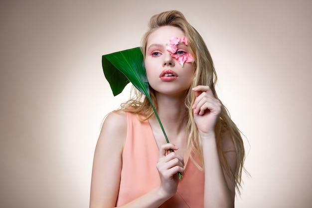 ピンクの花のメイク。大きな緑の葉を保持しているピンクの花のメイクと青い目の魅力的な若いモデル