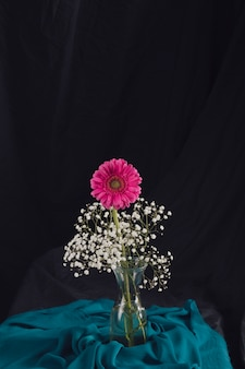 Pink flower with bloom twigs in vase near blue textile in darkness