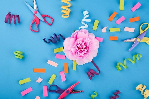 파란색 배경에 색종이와 가위가 있는 분홍색 꽃
