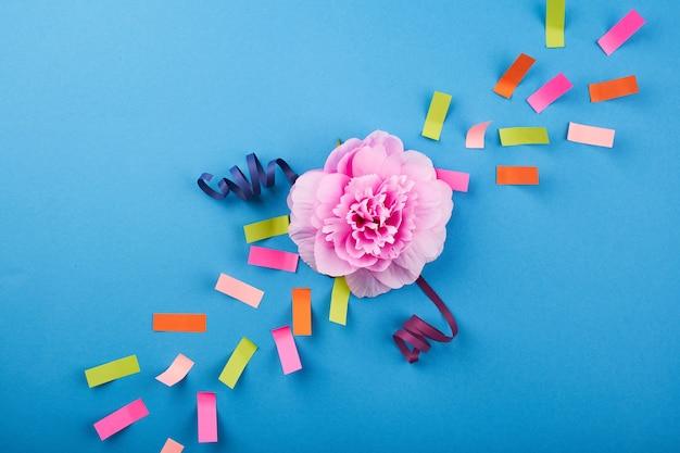 파란색 배경에 색종이가 있는 분홍색 꽃