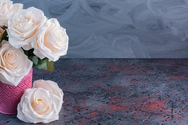 Un vaso di fiori rosa con fiori di rose bianche su grigio