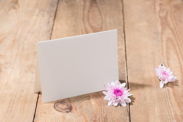 나무 배경에 있는 텍스트를 위한 분홍색 꽃과 빈 종이