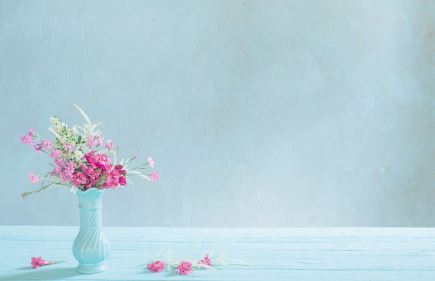 Pink flowers in blue vase on blue background