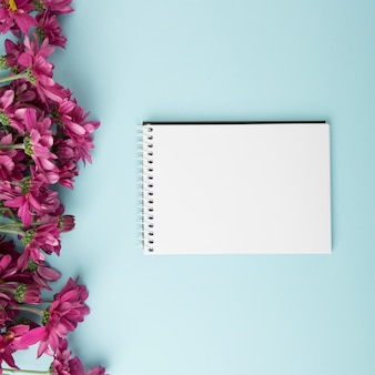 Pink flowers border and blank spiral notepad on blue background