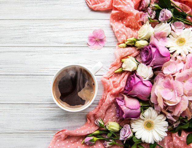 Pink flowers and cup of coffee on a white wooden background