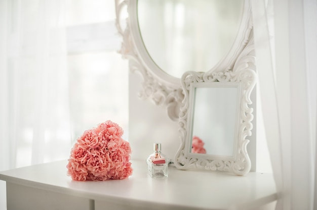Pink flowers on the dressing table in the white bedroom. flowers and perfumes in a bright interior