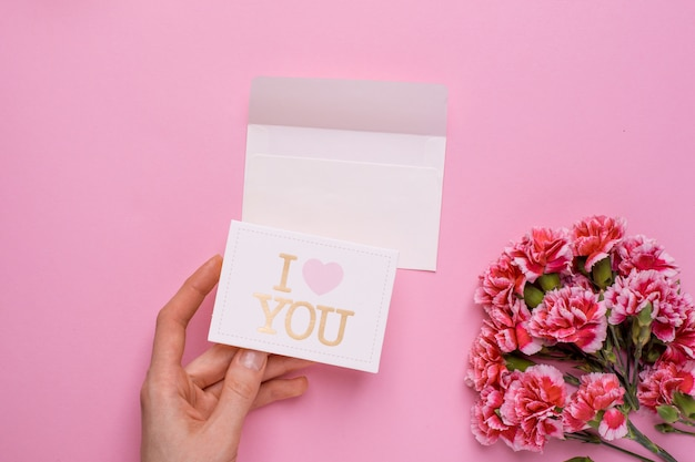 Pink flowers and hand with card i love you on pink