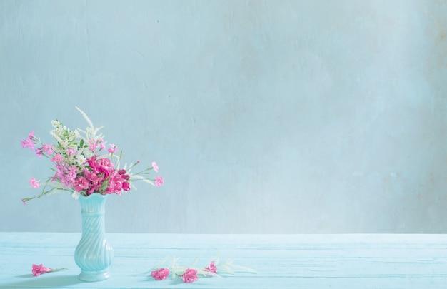 Розовые цветы в синей вазе на синем фоне