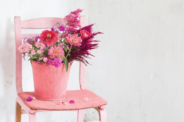 白いテーブルにバケツにピンクの花