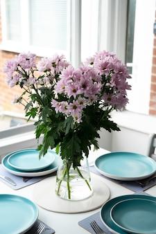 집에서 파란색 접시가 있는 현대적인 식탁에 있는 꽃병에 분홍색 꽃이 있습니다. 국화 핑크 꽃 꽃다발입니다.