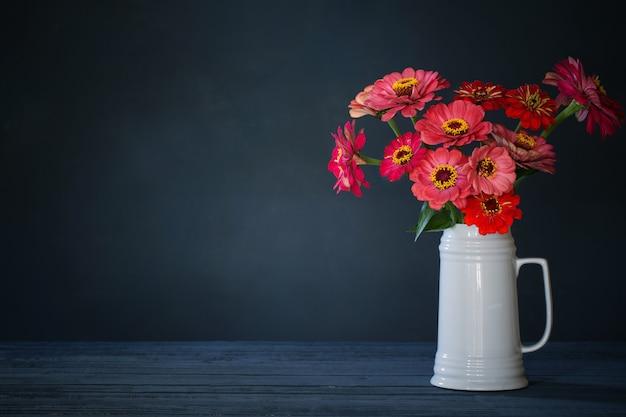 紺色の背景に白い水差しのピンクの花