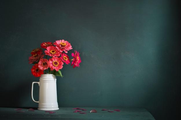 濃い緑色の背景に白い水差しのピンクの花
