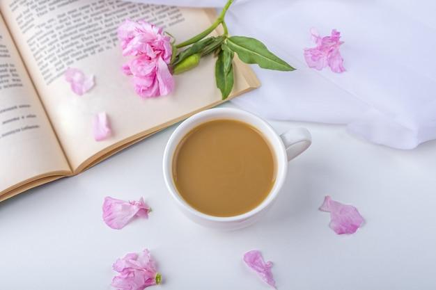 ピンクの花、古い本、お茶やコーヒーのカップ