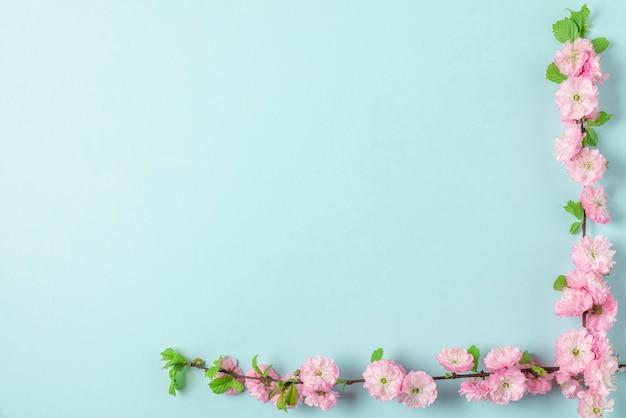 パステルブルーの背景にピンクの花。女性の日、母の日、バレンタインデー、結婚式のコンセプト。フラットレイ、コピースペース付きの上面図