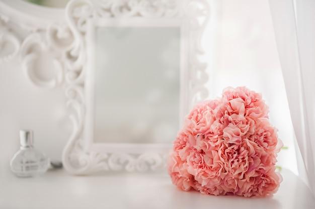 화이트 침실의 화장대에 핑크 꽃. 밝은 인테리어의 꽃과 향수