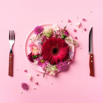 Pink flowers on pink plate, fork, knife over punchy pastel background.