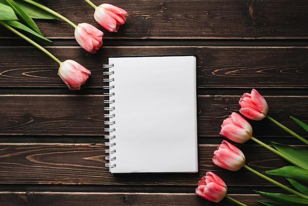 グリーティングカードの木製テーブルに空白のメモ帳でピンクの花チューリップ