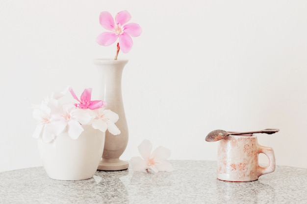 Pink flowers in a vase and cup of coffee