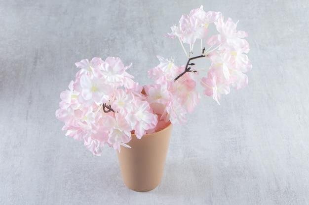 Fiori rosa in un vaso, su fondo bianco.