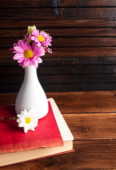 Pink flowers in white vase on book