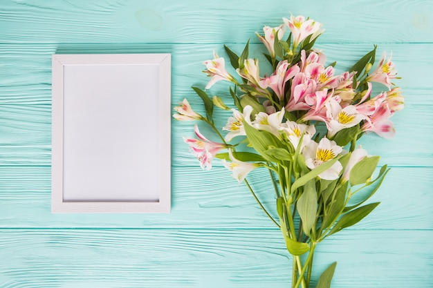 Pink flowers with blank frame on wooden table