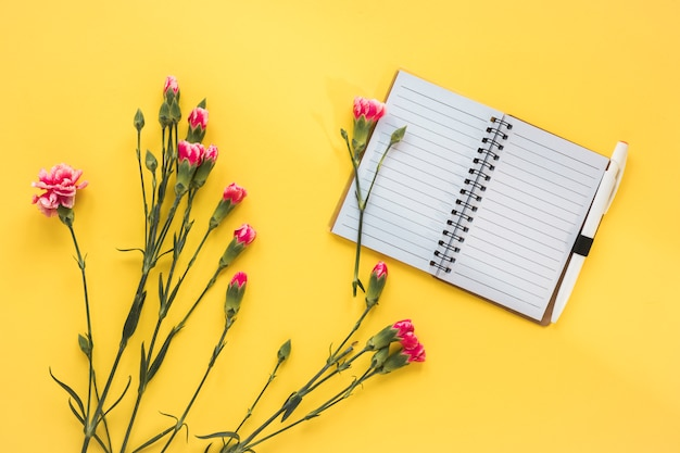 Pink flowers with blank notebook on table