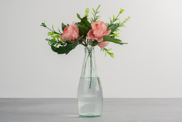 Pink flowers with green leaves in a glass vase