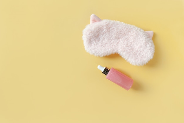 Pink fluffy fur sleep mask with small ears and bottle with serum for face on pastel yellow background