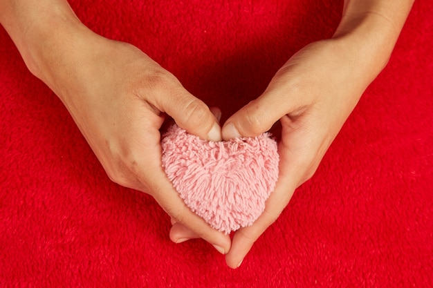 핑크 푹신한 플러시 하트. 젊은 여자는 빨간색 배경에 마음을 보유하고있다.