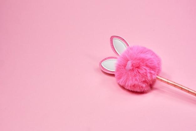 Розовый пушистый кролик в виде помпона и ручки на розовом фоне. креативный кроличий помпон с милыми ушками. копировать пространство. пасхальный кролик