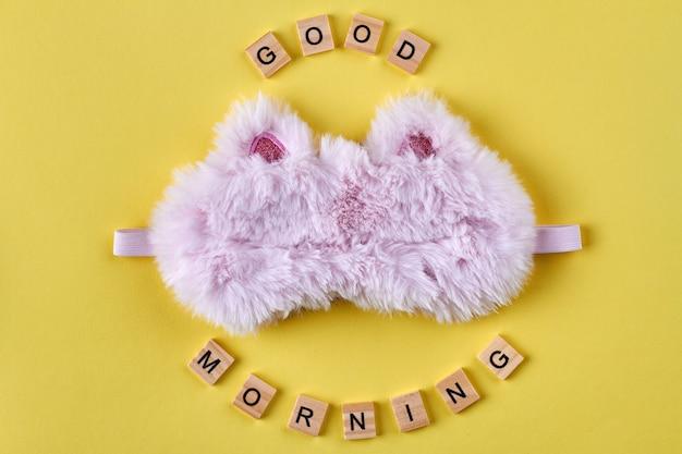 ピンクのふわふわの睡眠マスク。おはようコンセプト。黄色の背景の垂直ショット。