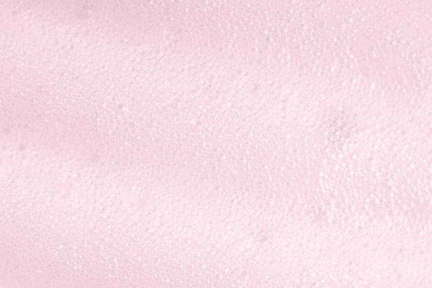 Pink foam macro background with bubbles. soapy surface closeup. foamy cleansing skin care product