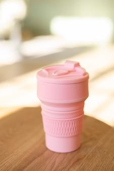 室内の廃棄物ゼロのスタイルでプラスチックなしのドリンク用のピンクの折りたたみ式シリコンカップ、クローズアップ。