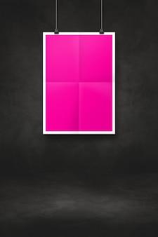 클립이 있는 검은색 벽에 걸려 있는 분홍색 접힌 포스터. 빈 모형 템플릿