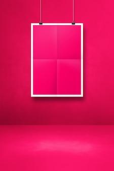 클립이 있는 깨끗한 벽에 핑크색 접힌 포스터가 걸려 있습니다. 빈 모형 템플릿