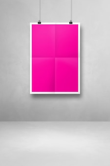 클립이 있는 흰색 벽에 걸려 있는 분홍색 접힌 포스터. 빈 모형 템플릿