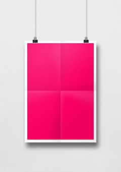 Pink folded poster hanging on a white wall with clips