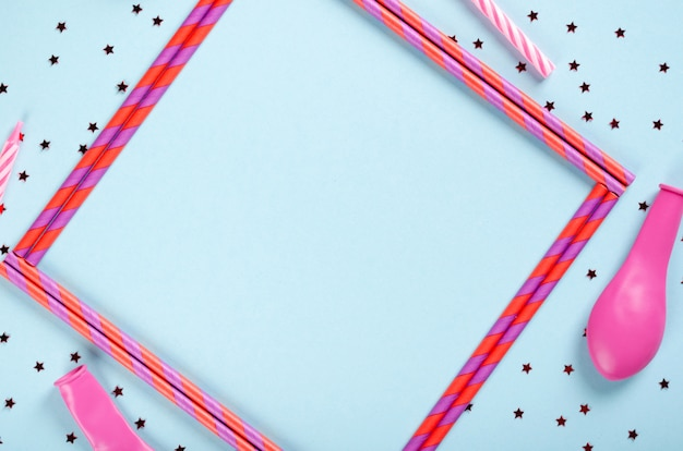 Pink frame from straw composition on blue background, party and celebration decoration.