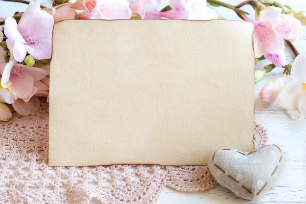 ピンクのフリージアの花、白い木製のテーブルの上の心と紙のコピースペースはコピースペースでクローズアップ