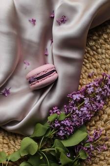 분홍색 프렌치 마카롱 또는 마카롱 쿠키와 천과 짚 스탠드 배경에 라일락 꽃. 천연 과일과 베리 맛, 크림 같은 속재료.