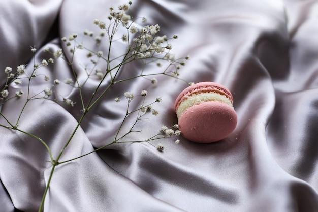 분홍색 프렌치 마카롱 또는 마카롱 쿠키와 천 배경에 흰색 꽃. 천연 과일과 베리 맛, 발렌타인 데이 부활절을 위한 크림 스터핑, 사랑의 음식.