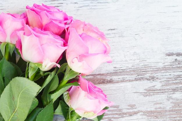 Розовые свежие розы белые деревянные в возрасте фон крупным планом