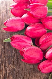 灰色の木製の背景にピンクの新鮮なチューリップの花。