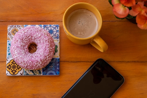 Pink frosted donut on the wooden table, coffee cup and cellphone - pause or breakfast