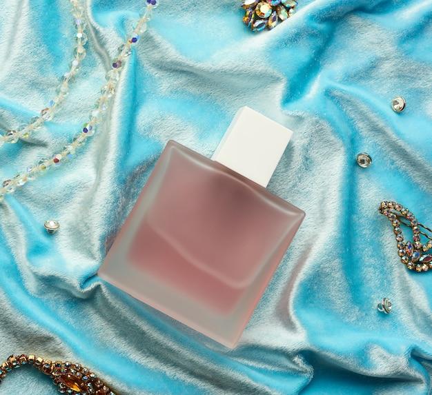 曇らされたガラスの香水とピンクのフルボトルは青い背景の上にあります